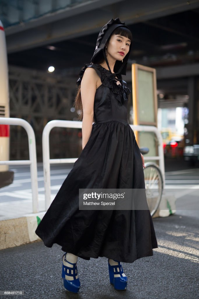 A guest is seen on the street wearing a black dress with black hat and blue heels during Tokyo Fashion Week on March 25, 2017 in Tokyo, Japan.