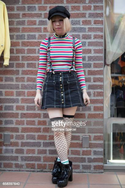 A guest is seen on the street wearing a black hat pink/blue striped shirt denim skirt fishnet stockings and black shoes during Tokyo Fashion Week on...