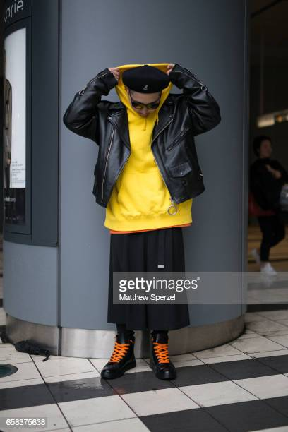 A guest is seen on the street wearing a black leather jacket with yellow hoodie and orange shirt black beret and black and orange boots during Tokyo...
