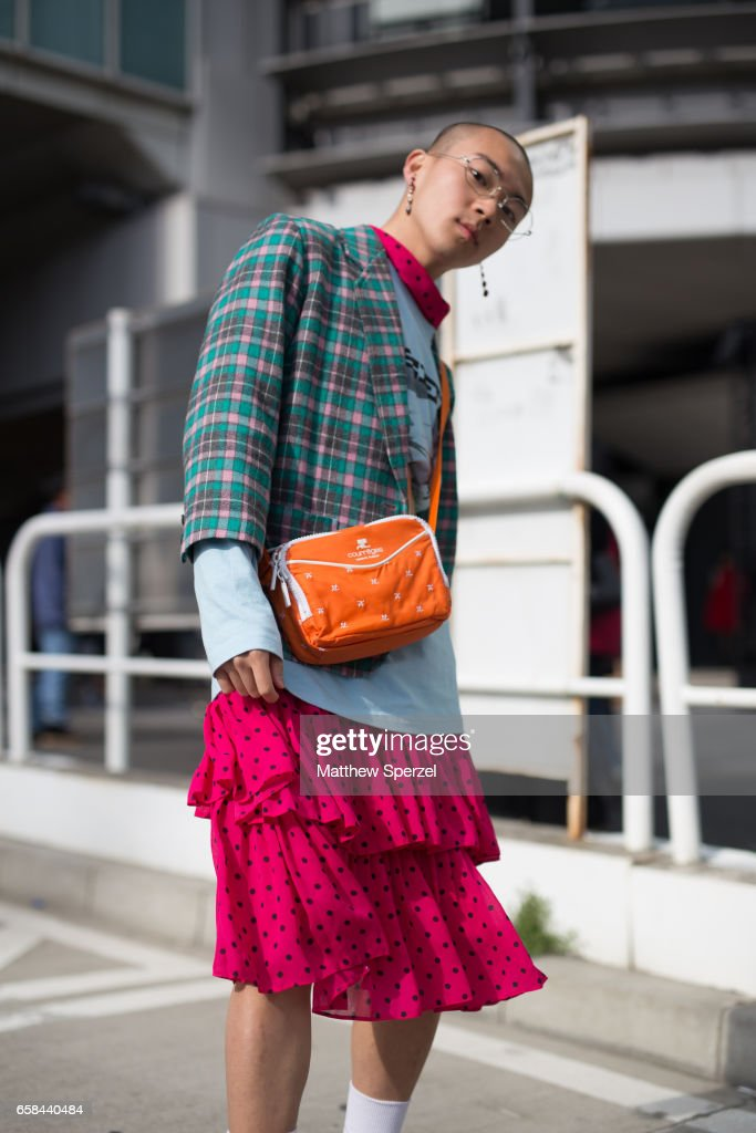 A guest is seen on the street wearing a blue plaid jacket, blue shirt, orange bag, and pink polka dot skirt during Tokyo Fashion Week on March 24, 2017 in Tokyo, Japan.