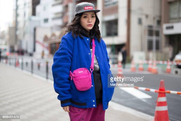 A guest is seen on the street wearing a blue varsity jacket with pink crossbody bag and Supreme hat during Tokyo Fashion Week on March 25 2017 in...