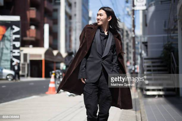 A guest is seen on the street wearing a brown coat with grey suit during Tokyo Fashion Week on March 24 2017 in Tokyo Japan