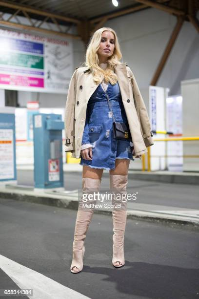 A guest is seen on the street wearing a cream coat blue denim dress and cream thighhigh heels during Tokyo Fashion Week on March 20 2017 in Tokyo...