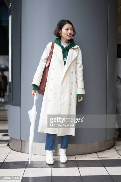 A guest is seen on the street wearing a cream long coat green hoodie white shirt and blue jeans with white shoes during Tokyo Fashion Week on March...