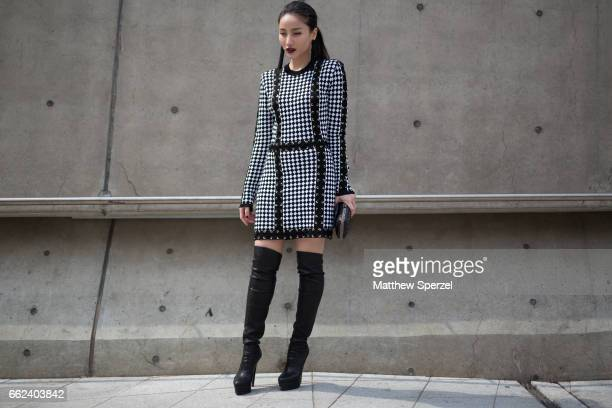 A guest is seen on the street wearing a navy/white checker dress with black kneehigh boots during HERA Seoul Fashion Week on March 29 2017 in Seoul...