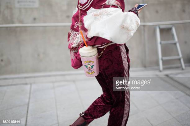 A guest is seen on the street wearing a pink shirt red/white satin jacket red track pants and pink hat and bag during HERA Seoul Fashion Week on...