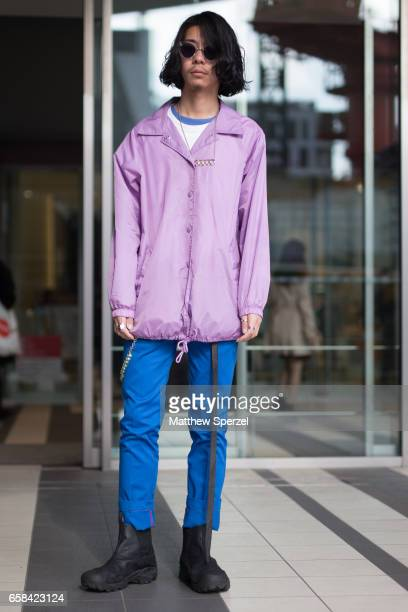 A guest is seen on the street wearing a purple jacket with blue pants during Tokyo Fashion Week on March 23 2017 in Tokyo Japan