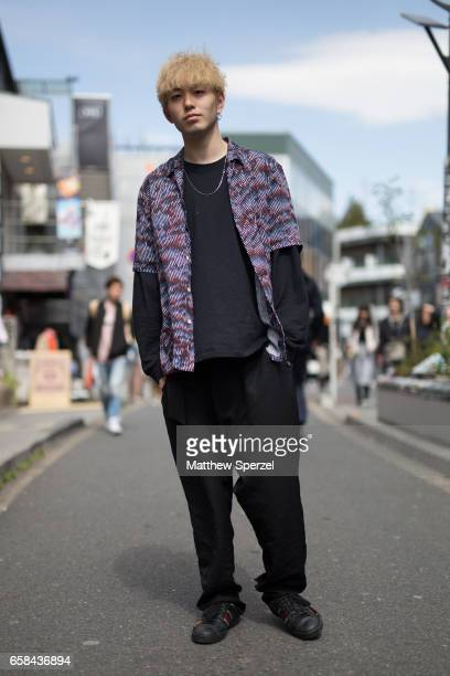 A guest is seen on the street wearing a purple shirt with black sweater and pants during Tokyo Fashion Week on March 24 2017 in Tokyo Japan