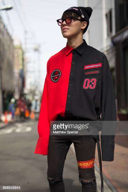 A guest is seen on the street wearing a red and black oversized shirt with black beanie and black pants with black and red boots during Tokyo Fashion...
