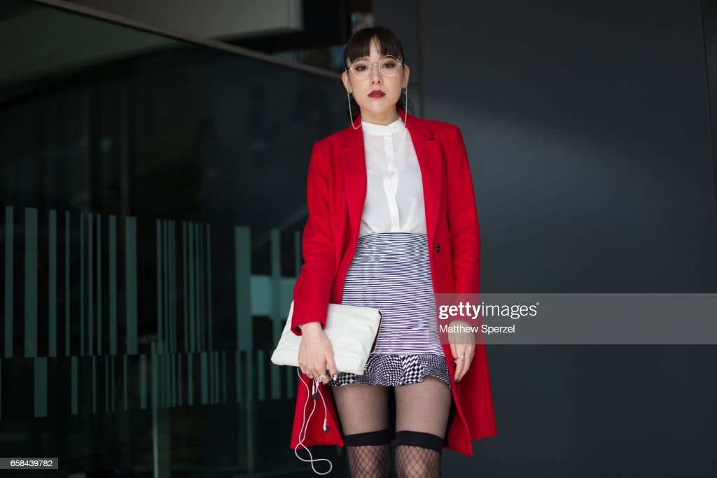 A guest is seen on the street wearing a red coat, striped skirt, and white shirt with white bag during Tokyo Fashion Week on March 24, 2017 in Tokyo, Japan.