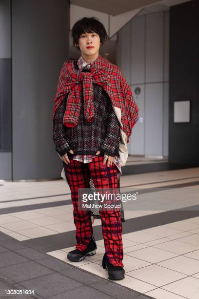 Guest is seen on the street wearing a red plaid tied jacked, fishnet shirt, red plaid pants and shirt, black boots during the Rakuten Fashion Week...