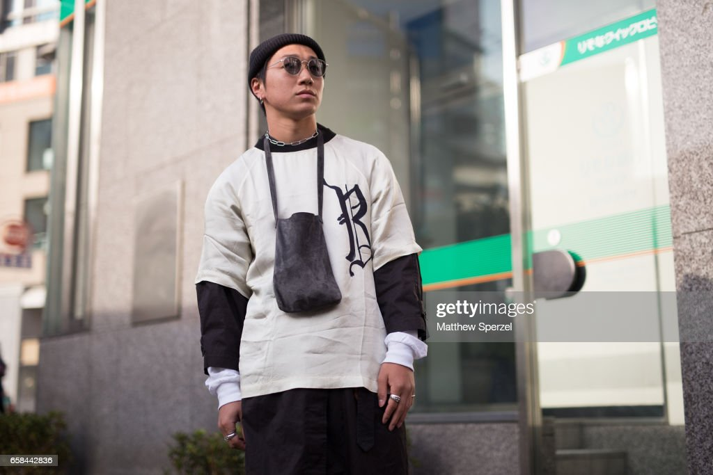 A guest is seen on the street wearing a white and black shirt with black shirt, white shirt, and black pants during Tokyo Fashion Week on March 24, 2017 in Tokyo, Japan.
