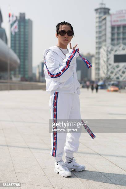 A guest is seen on the street wearing a white Champion sweatsuit Fila shirt and white sneakers during HERA Seoul Fashion Week on March 29 2017 in...