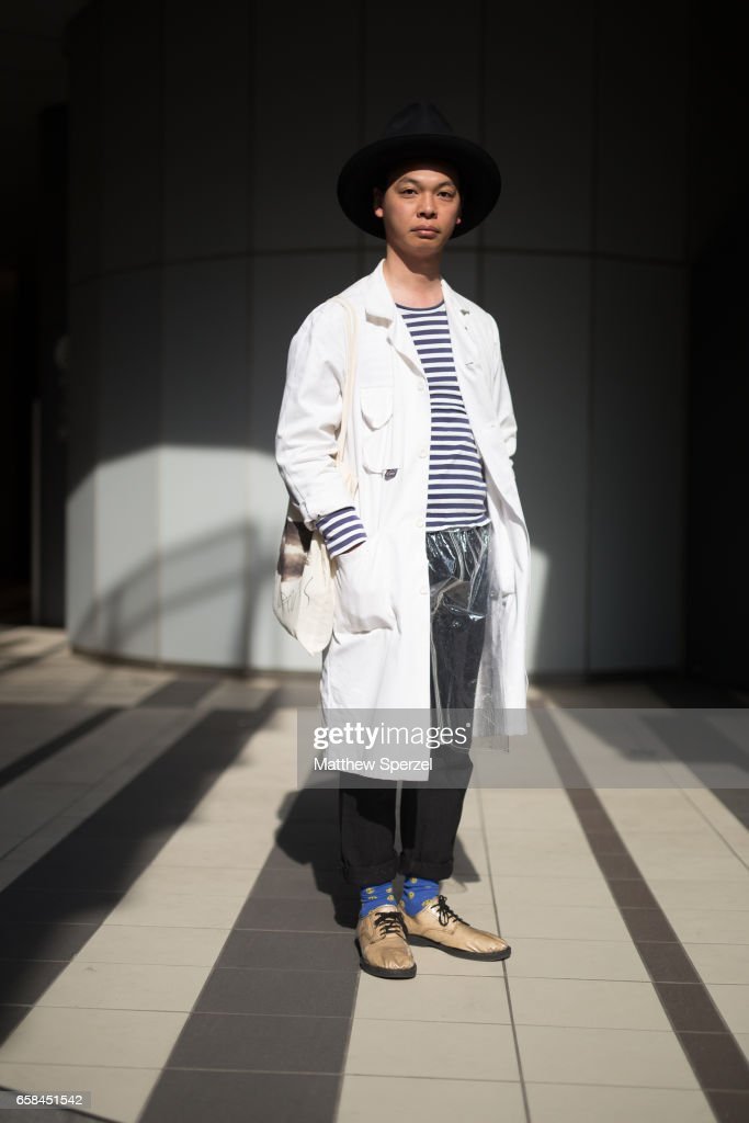 A guest is seen on the street wearing a white coat, black/white stripe shirt, black pants, blue socks, and tan shoes with black brimmed hat during Tokyo Fashion Week on March 25, 2017 in Tokyo, Japan.