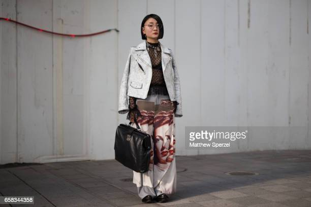 A guest is seen on the street wearing a white denim jacket with black bag and face print pants during Tokyo Fashion Week on March 20 2017 in Tokyo...