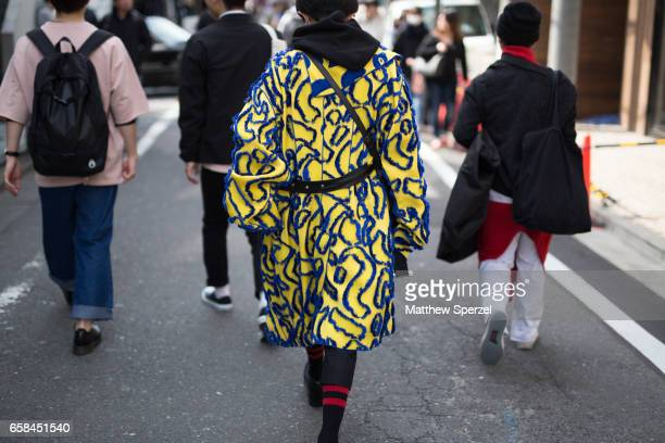 A guest is seen on the street wearing a yellow and blue pattern jacket during Tokyo Fashion Week on March 25 2017 in Tokyo Japan