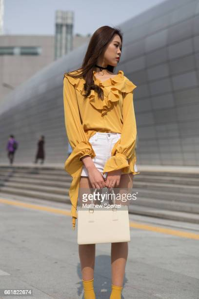 A guest is seen on the street wearing a yellow frilly top white shorts silver shoes with yellow socks offwhite bag during HERA Seoul Fashion Week on...