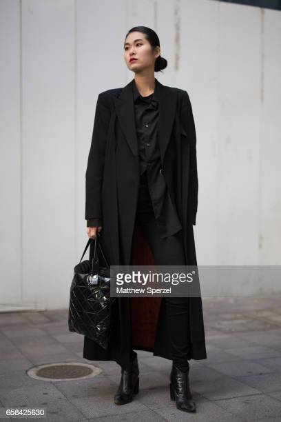 Guest is seen on the street wearing an all-black outfit with a long black coat during Tokyo Fashion Week on March 23, 2017 in Tokyo, Japan.