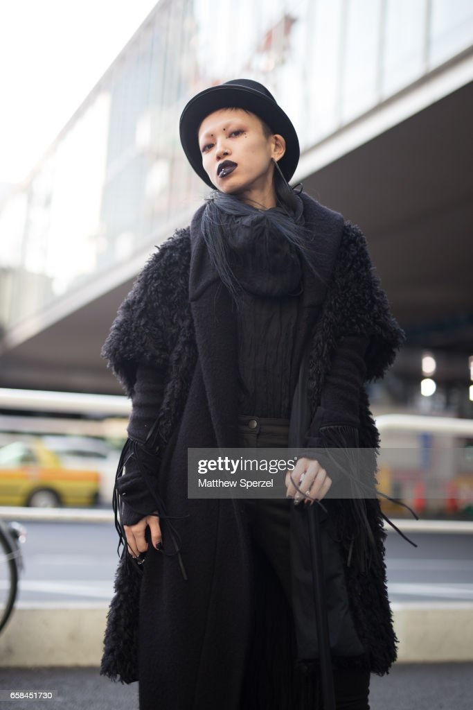 A guest is seen on the street wearing an all-black outfit with fringe jacket and black hat and cane during Tokyo Fashion Week on March 25, 2017 in Tokyo, Japan.