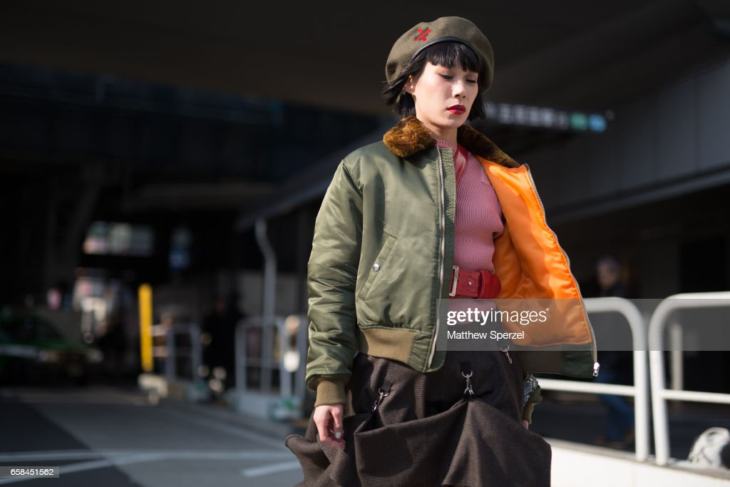 A guest is seen on the street wearing an army green beret, orange/green bomber jacket, pink sweater, red belts, brown skirt, and black heeled boots during Tokyo Fashion Week on March 25, 2017 in Tokyo, Japan.