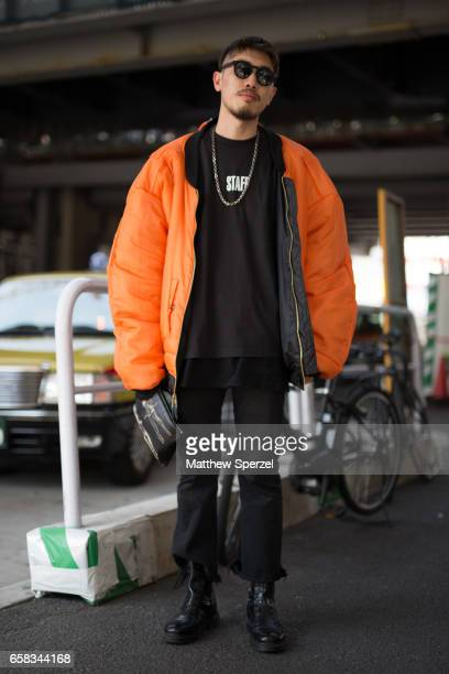 A guest is seen on the street wearing an orange ski jacket with black sweater and mirrored sunglasses during Tokyo Fashion Week on March 20 2017 in...