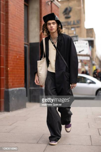 A guest is seen on the street wearing black jacket and pants with cream sweater and black hunting hat during London Fashion Week Men's January 2019...