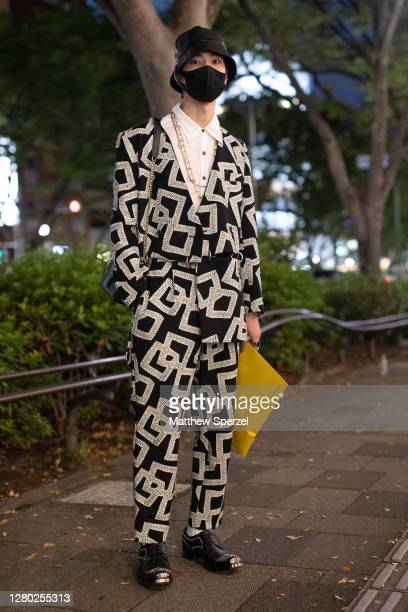 A guest is seen on the street wearing black/silver square print suit white shirt gold necklace black bucket hat yellow bag black face mask and shoes...