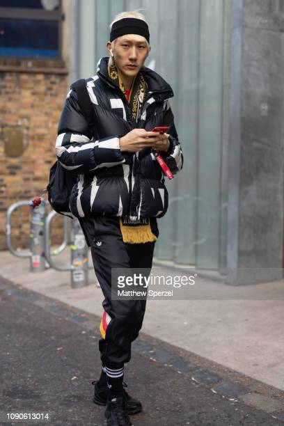 A guest is seen on the street wearing black/white design down coat black headband yellow scarf black track pants with Adidas sneakers during London...