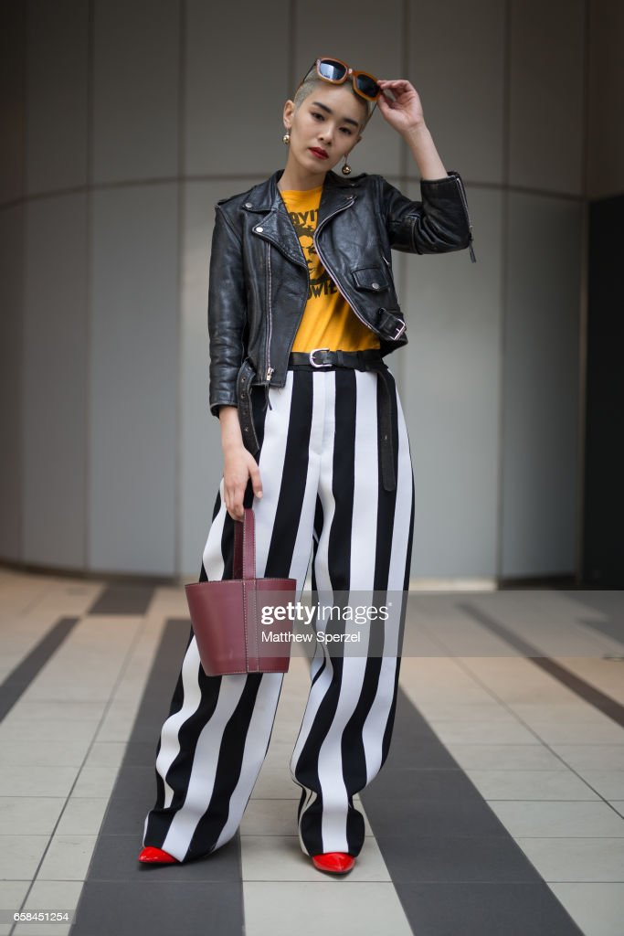 A guest is seen on the street wearing black/white striped pants, red shoes, yellow shirt, and black leather jacket during Tokyo Fashion Week on March 25, 2017 in Tokyo, Japan.