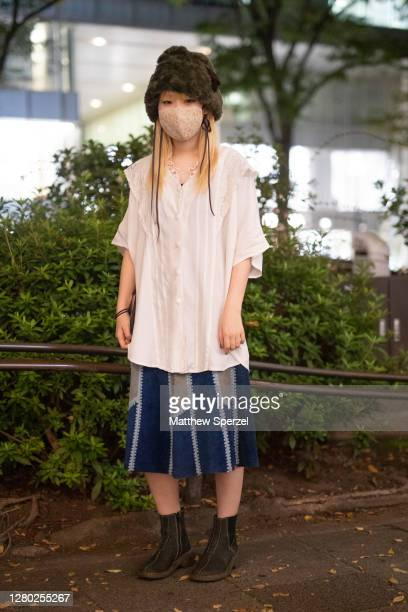 A guest is seen on the street wearing faux fur hat embroidered face mask white lace detail top navy pattern skirt and black boots during the Rakuten...