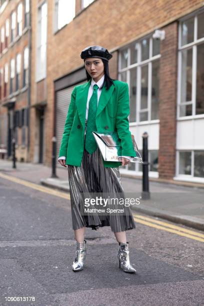A guest is seen on the street wearing green blazer and tie with silver pleated skirt white shirt silver metallic shoes and black beret during London...