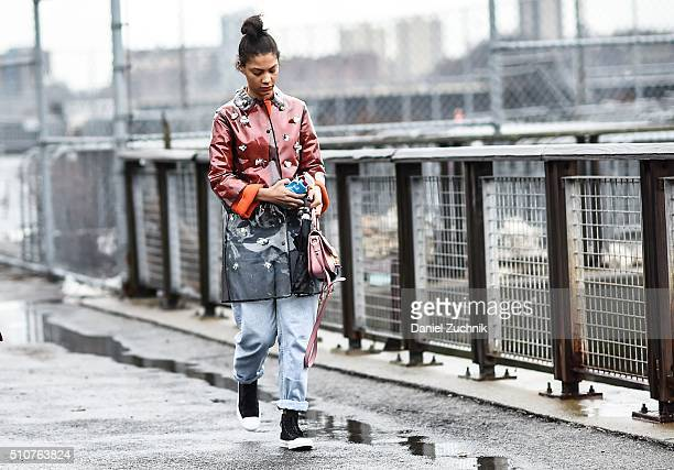 A guest is seen outside the Coach show wearing a see through raincoat during New York Fashion Week Women's Fall/Winter 2016 on February 16 2016 in...