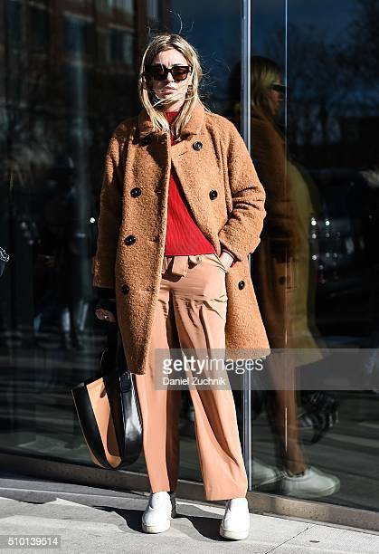 A guest is seen outside the Tibi show wearing a brown coat red sweater and brown pants with white shoes during New York Fashion Week Women's...