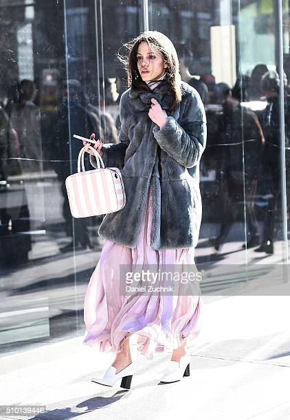 A guest is seen outside the Tibi show wearing a grey fur coat and pink dress during New York Fashion Week Women's Fall/Winter 2016 on February 13...