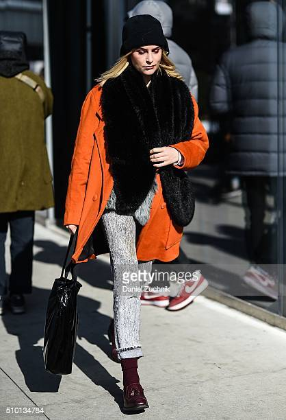 A guest is seen outside the Tibi show wearing an orange coat with a black oversized scarf during New York Fashion Week Women's Fall/Winter 2016 on...