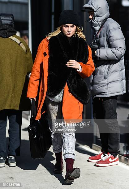 Guest is seen outside the Tibi show wearing an orange coat with a black oversized scarf during New York Fashion Week: Women's Fall/Winter 2016 on...