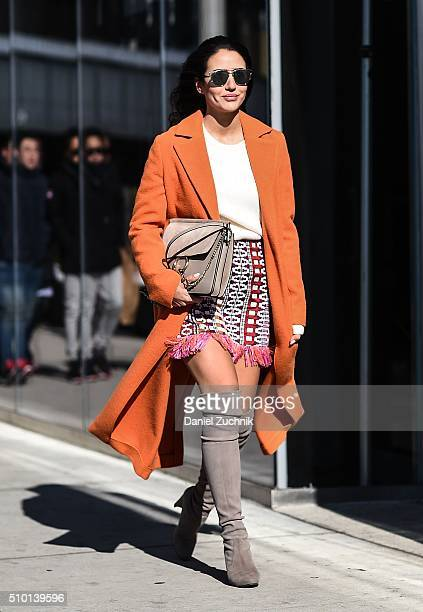A guest is seen outside the Tibi show wearing an orange coat with a graphic fringe skirt during New York Fashion Week Women's Fall/Winter 2016 on...