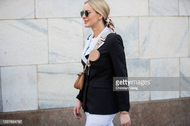 A guest is seen outside wearing brown bag Vivetta during Milan Fashion Week Fall/Winter 20202021 on February 20 2020 in Milan Italy
