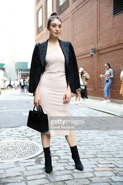 A guest is seen posing with a black blazer white dress black purse and boots at Spring Studios during New York Fashion Week on September 11 2019 in...