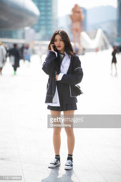 A guest is seen talking on her phone wearing pleated mini skirt at the Hera Seoul Fashion Week 2019 F/W at Dongdaemun Design Plaza at Dongdaemun...