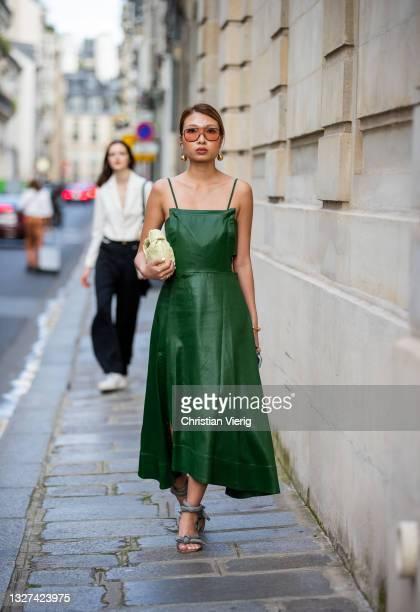 Guest is seen talking on wearing Bottega Veneta bag green dress outside Armani on July 06, 2021 in Paris, France.