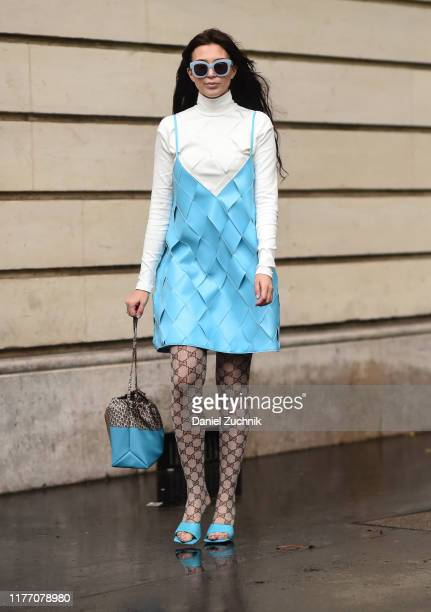 A guest is seen wearing a baby blue dress white sweater and blue bag and sunglasses outside the Lanvin show during Paris Fashion Week SS20 on...