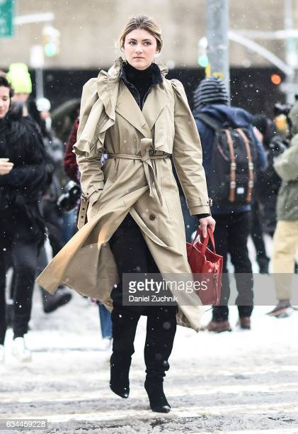 A guest is seen wearing a beige coat and red bag outside of the Brock Collection show during New York Fashion Week Women's Fall/Winter 2017 on...