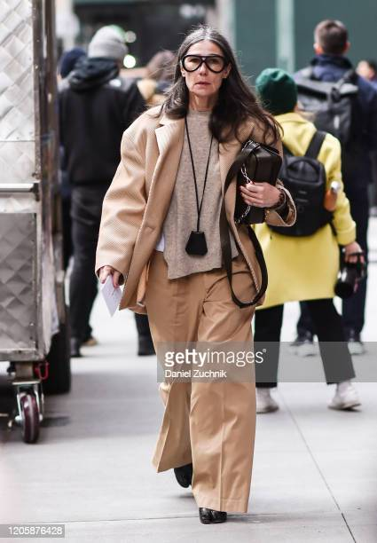 Guest is seen wearing a beige coat, beige pants, gray sweater and black bag outside the Michael Kors show during New York Fashion Week: A/W20 on...