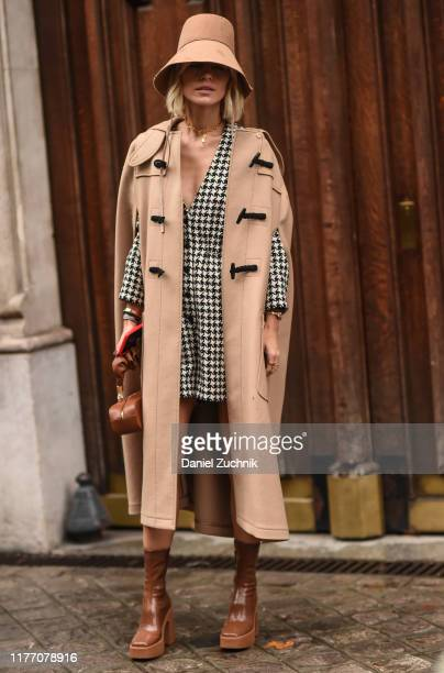 A guest is seen wearing a beige Lanvin coat beige hat and black and white checkered dress with brown leather boots outside the Lanvin show during...