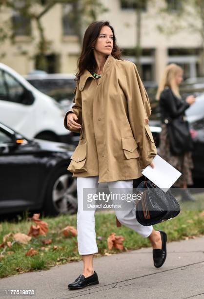 Guest is seen wearing a beige top and white pants outside the Loewe show during Paris Fashion Week SS20 on September 27, 2019 in Paris, France.