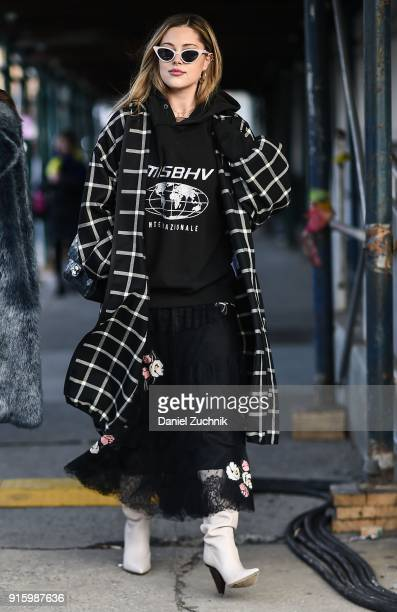 A guest is seen wearing a black and white checkered coat and Misbhv sweatshirt outside the Tadashi Shoji show during New York Fashion Week Women's...
