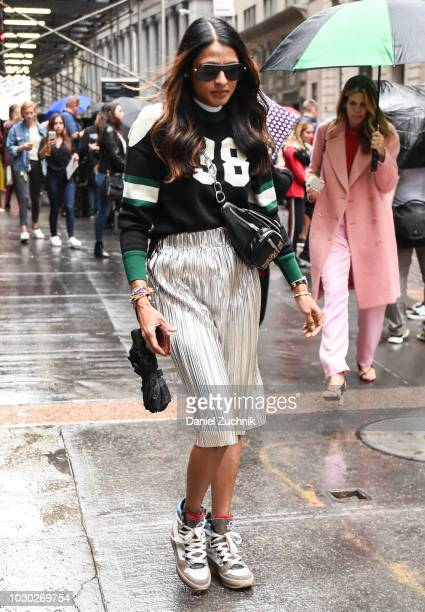 A guest is seen wearing a black and white jersey top silver skirt and Moncler shoes outside the Tibi show during New York Fashion Week Women's S/S...