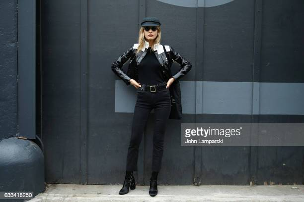 A guest is seen wearing a black and white leather jacket and hat jeans and booties outisde the Nautica fashion show during New York Men's Fashion...