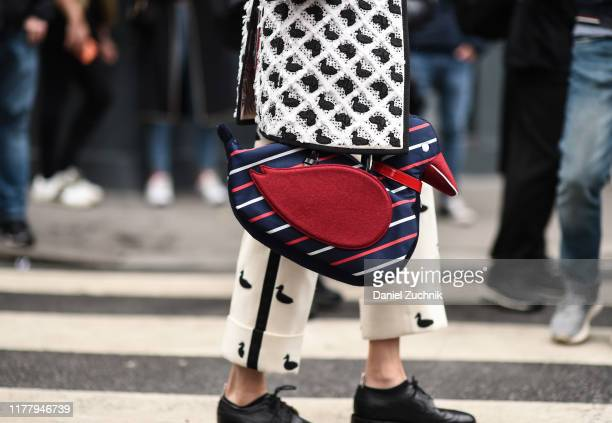 Guest is seen wearing a black and white Thom Browne coat, pants and gray Thom Browne cardigan with a Thom Browne duck bag outside the Thom Browne...